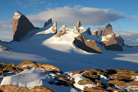 Erhabene Momente: Mitternachtspanorama einer bizarren Gebirgslandschaft in der Antarktis. Mit Holtanna (2.650 m), Holstind, Kientanna und Ulvetanna (2.931 m) (v.l.n.r.). [Photo] Alexander Huber collection